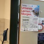Foto: Plakat zum Fachtag urbanes Lernen in Freiburg an der Tür zu einem Klassenzimmer der Grundschule.