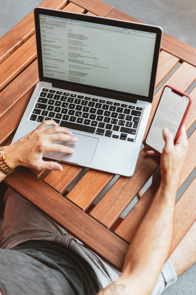 Das Foto zeigt eine Person am Laptop und Smartphone, die eine Onlinebestellung aufgeben will.